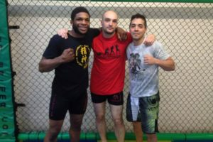 mma coach stands with Bellator champion and teammate in a cage in the UK
